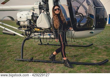 Full Length Portrait Of Preteen Girl In Sunglasses Standing Near Helicopter Cockpit