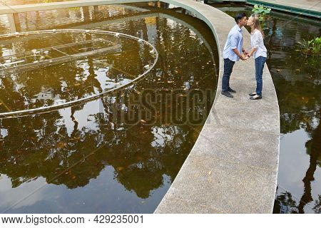 Happy Young Multi-ethnic Couple In Love Holding Hands And Kissing When Walking In City Park