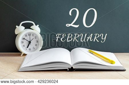February 20. 20-th Day Of The Month, Calendar Date.a White Alarm Clock, An Open Notebook With Blank
