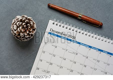 December 2021 - spiral desktop calendar with a decorative frosted pine cone, time and business concept