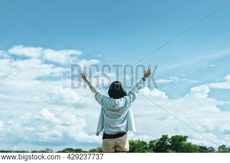 Copy Space Of Woman Rising Hands On Blue Sky White Clouds At Nature Green Field Abstract Background.