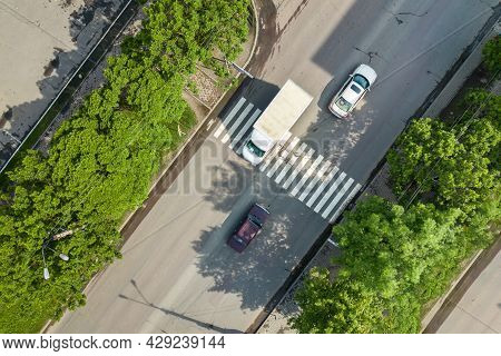 Top Down Aerial View Of Busy Street With Moving Cars Traffic And Zebra Road Pedestrian Crosswalk.