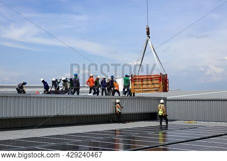 Crane Uploading Solar Pv Panels On Roof With Installation Workers