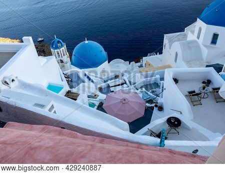 View From Viewpoint Of Oia Village With Blue Domes Of  Greek Orthodox Christian Churches And Traditi