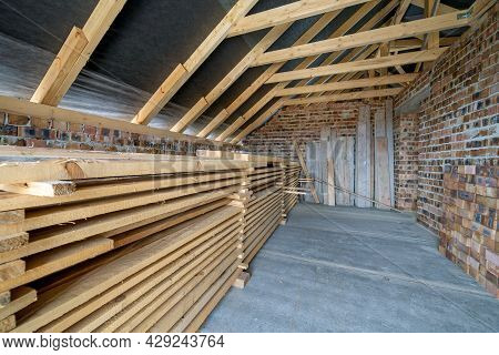 Stack Of Wooden Boards In Unfinished Brick House With Concrete Floor, Bare Walls And Wooden Roofing