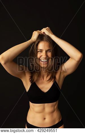 Portrait Of Young Beautiful Slim Tanned Woman In Black Lingerie Posing Isolated Over Dark Studio Bac