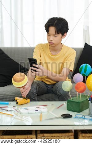 Serious Teenage Boy Taking Photo Of Jupiter Styrofoam Planet He Made For School On Smartphone And Po