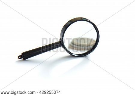 Magnifier And Stack Of Coins Isolated On White Background. Concept Of Keeping Money, Investing
