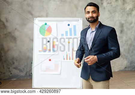 Smart And Intelligent Indian Man In Suit Stands Near Whiteboard With Diagrams, Looks At The Camera,