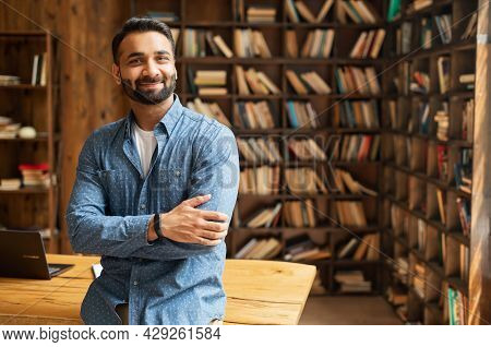 Smiling Bearded Indian Businessman Stands Near Desk And Looks At The Camera. Young Positive Male Stu