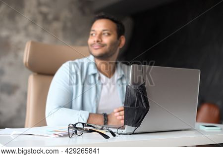 Excited Smart Smiling Young Indian Freelancer Guy Sits On The Workplace And Using Laptop Computer Wo