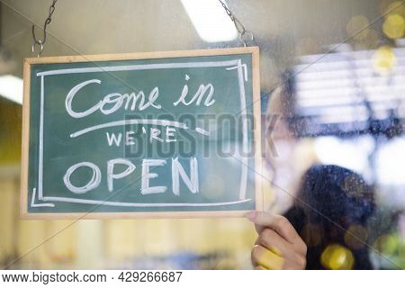 Welcome. Open. Barista, Waitress Woman Turning Open Sign Board On Glass Door In Modern Cafe Coffee S