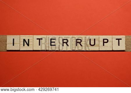 Text The Word Interrupt From Gray Wooden Small Letters With Black Font On An Red Table