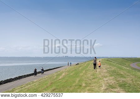 Oudeschild, Netherlands, 19 July 2021: People Walk And Ride Bicycle On Dike Near Oudeschild On The D