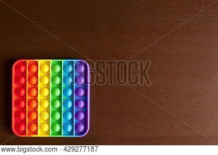 Kids Anti Stress Sensory Pop It Or Simple Dimple Fidget Push Toy On A Black Table Or Floor Backgroun