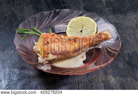 Ocean Perch Cooked In Sour Cream Sauce On A Red Glass Plate On A Dark Surface