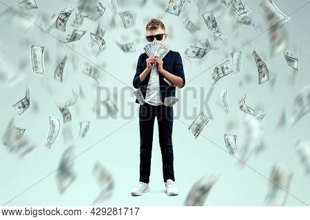 A Cute, Rich Boy With Glasses Holds Dollars And Knows How To Make Money Against The Background Of Fa