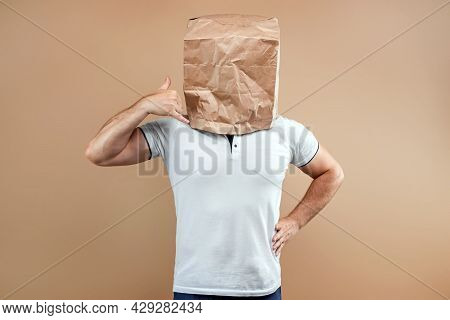 Men Put A Paper Bag Over Their Heads, Pretending To Ring A Non-existent Phone. Isolated On Yellow Ba