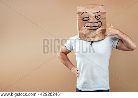 A Man With A Paper Bag On His Head, On Which An Evil Face Is Painted, Pretends To Be On The Phone. I