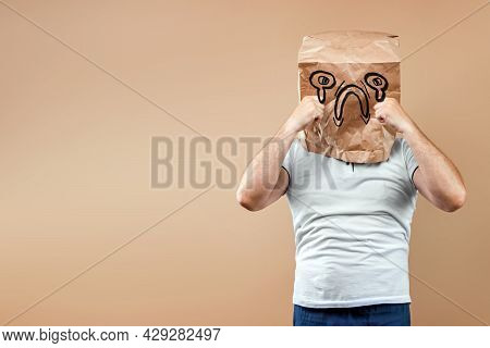 Men Put A Paper Bag On Their Heads, On Which A Crying Face, Upset, Bad Mood Is Drawn. Isolated On Ye