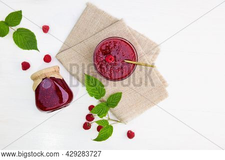Raspberry Jam In A Glass Jar And Bowl On A Linen Napkin On A White Wood Background. Conservation And