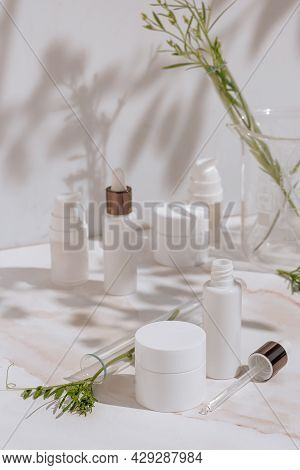 Natural Cosmetic Products In White Packaging With Laboratory Glassware. Science And Skincare Concept