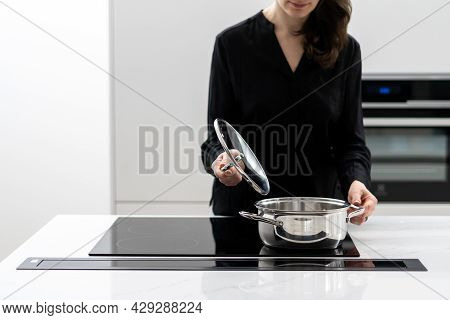 Cropped Shot Of Woman In Black Shirt Holding Lid Over Pot And Checking State Of Food, Cooking On Bui