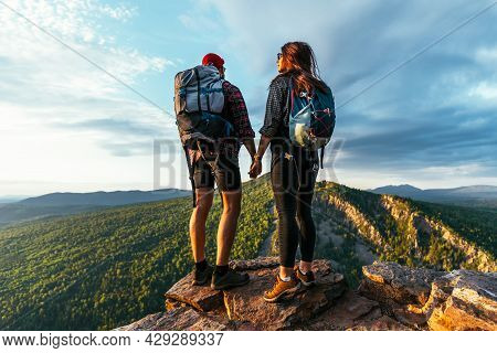 A Man And A Woman In Tourist Equipment Are Standing On A Rock And Admiring The Panoramic View. Two T
