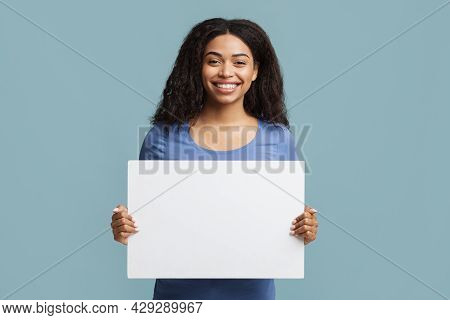 Place For Your Ad. Cheerful Black Woman Holding Blank Placard With Free Space For Advertisement Over