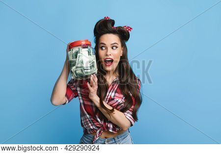Banking, Investments, Financial Success. Excited Pinup Lady Holding Jar Of Money On Blue Studio Back