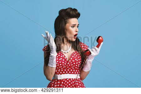 Shocked Young Pinup Woman In Retro Dress Holding Landline Phone Receiver, Feeling Irritated About Te