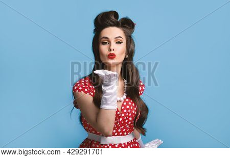 Sexy Young Pinup Woman In Old Fashioned Dress And Gloves Blowing Air Kiss At Camera Over Blue Backgr