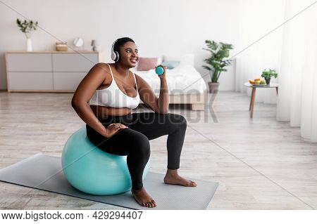 Overweight Afro Woman Exercising With Dumbbells, Sitting On Fitball, Listening To Music In Headphone