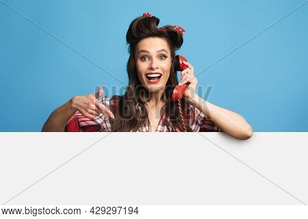 Call Me. Happy Young Pinup Woman In Retro Wear Pointing At Blank Advertisement Board, Speaking On La