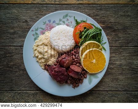 Lunch Plate With Traditional Brazilian Feijoada And Wooden Background.