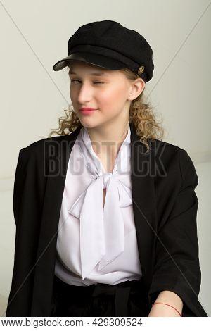 Portrait Of Elegant Pretty Girl Blinking One Eye. Beautiful Stylish Young Woman In Fashionable Black