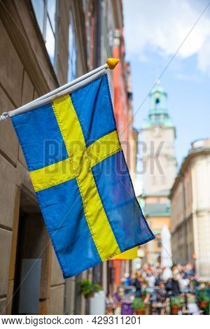 Street in Stockholm with swedish flag, Sweden. Focus on the flag