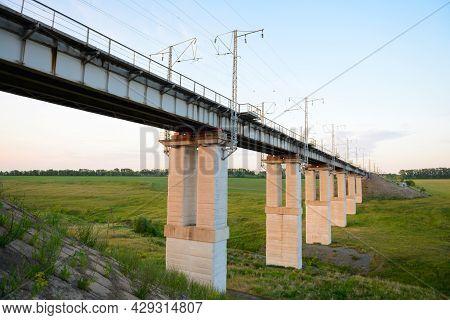 Modern Railway Bridge Over The Green Ravine On A Summer Evening