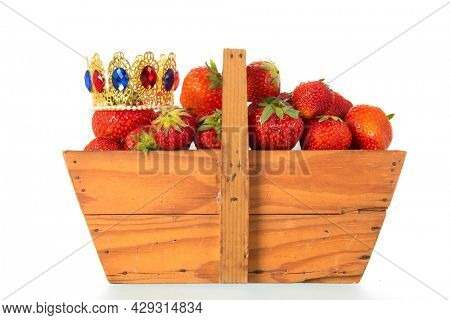 wooden harvest basket full with crowned strawberries isolated over white background