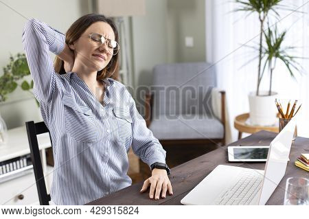 Freelancer Young Woman Suffering With Neck Pain Massaging Her Neck While Working In Her Office At Ho