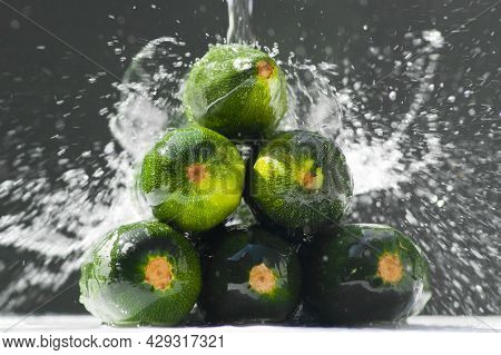 Wet Zucchini On A Dark Background. Zucchini With Splashing Water Are Stacked In A Heap On A Black Ba