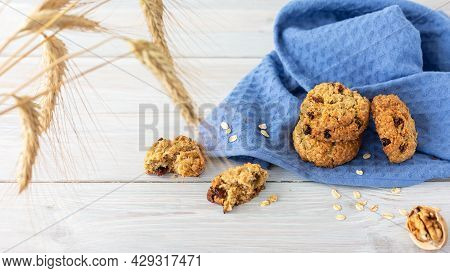 Homemade Oatmeal Cookies With Raisins, Half Walnut On Wooden Background And  Blue Napkin. Concept: H