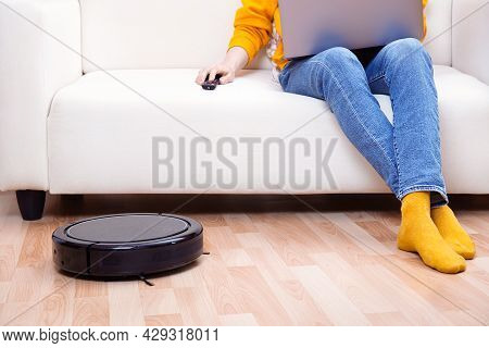Man Working On Remote Work Using Laptop , While The Robot Vacuum Cleaner Cleaning Living Room And Du