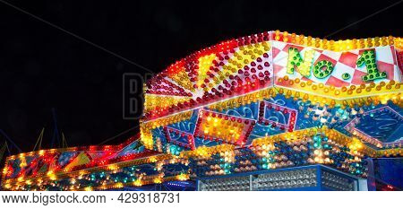 A Bright Facade Of Glowing Multi-colored Light Bulbs Against The Background Of The Night Sky. Close-
