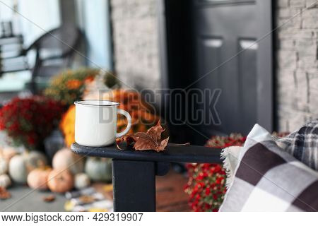 Steaming Coffee Cup Sitting On Arm Of Rocking Chair On A Front Porch That Has Been Decorated For Aut