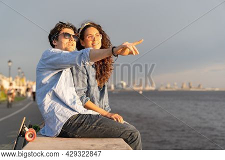 Carefree Man And Woman Watching Sunset At Seaside Together Sitting On Concrete Pavement Look At Sky.