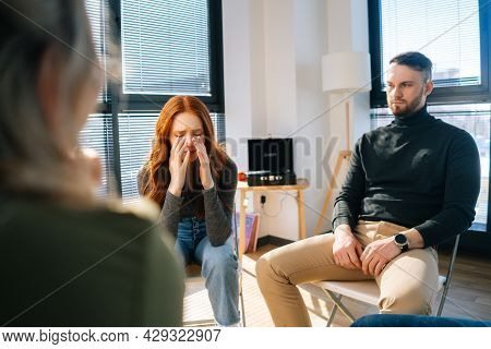 Portrait Of Sad Crying Young Woman Sharing Problem Sitting In Circle During Group Therapy Session. D