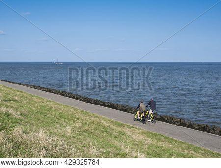 Oudeschild, Netherlands, 19 July 2021: Couple Rides Bicycle On Dike Of Wadden Sea On Dutch Island Of