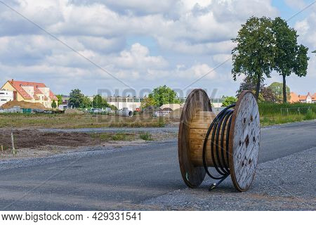 A Nearly Empty Wooden Reel With The Remains Of A Black Cable On A Construction Site. Cloudy Sky.