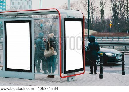 Two Blank Advertising Billboard At The Glass Bus Stop On A Street Full Of People. Crowd. Winter. Col